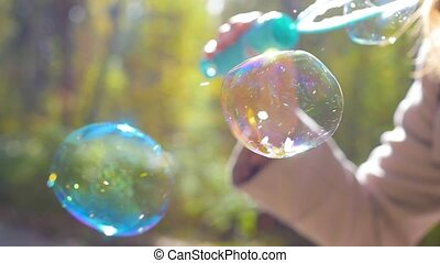 girl blowing large soap bubbles closeup in sunlight
