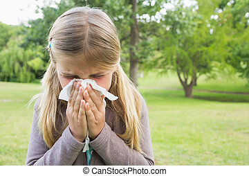 Girl blowing nose with tissue paper at park - Close-up of a...