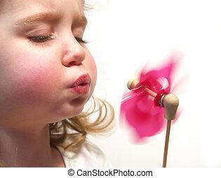 little girl blowing a pink pinwheel