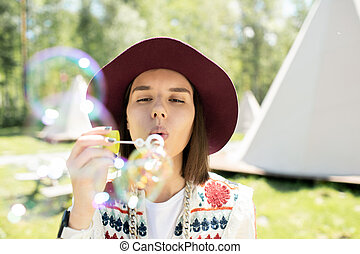 Girl blowing soap bubbles outdoors - Pretty girl standing ...