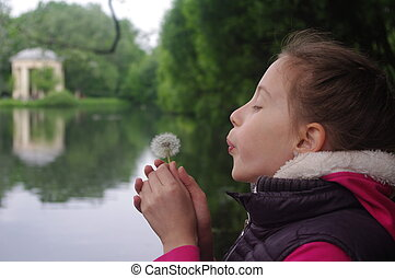 girl blowing to dandelion flower
