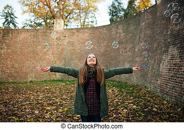 Girl blows balloons.