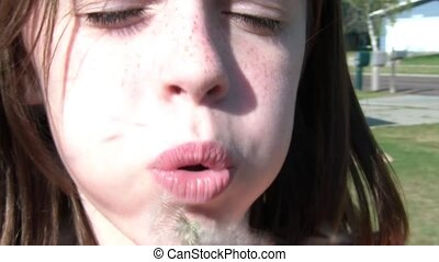Girl Blows Dandelion Seeds at Camera