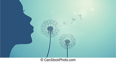 girl blows dandelion silhouette on blue sky background