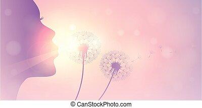 girl blows dandelion silhouette on sunny sky