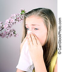 Girl blows her nose with handkerchief, cherry blossoms