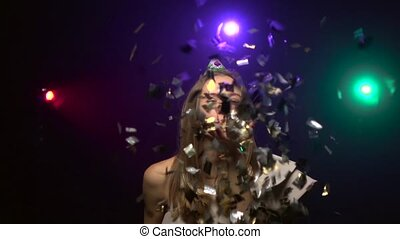 Girl blows off confetti, blowing party whistle. Close-up....