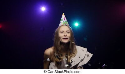 Girl blows off confetti with palms, blowing party whistle,...
