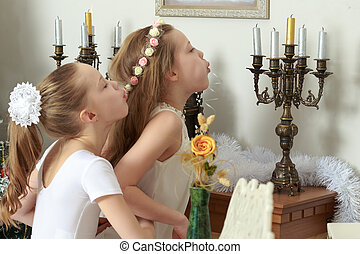 Girl blows out the candles on the mantelpiece.