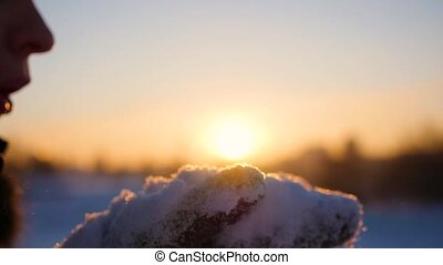 girl blows snow with hands at sunset background. Winter frosty day