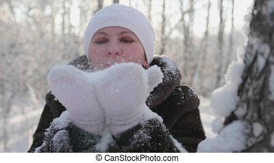 Girl blows snowflakes with his hands. A walk in the winter