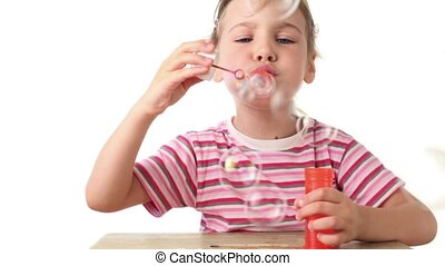 Girl blows soap bubbles and catch one by stick and shows it