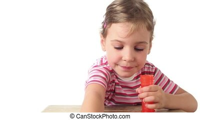 Girl blows soap bubbles and tries to catch them by stick,...