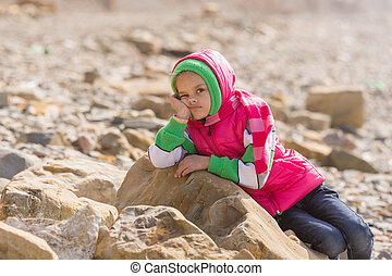 Girl bored at the seaside in the offseason lay down on a big rock