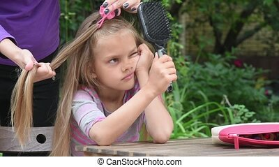 Girl bored until my mother braids her long hair and looking...