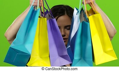 Girl bought a lot of things in her hands with her shopping bags. Green screen. Close up. Slow motion