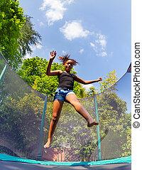 Girl bouncing up on backyard trampoline in summer