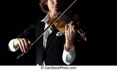 Girl bows a violin in a dark room. Black background. Close up