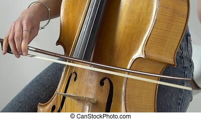 Girl bows the cello strings to play a lyrical composition....