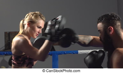 Girl boxer is coached by a man. Boxing sparring in the ring. Slow motion
