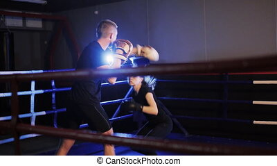girl boxer talking with coach in gym - young woman boxer...