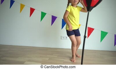 Girl boxing on a boxing pear. Active playful child have fun at home. Gimbal stabilizer camera movement up shot
