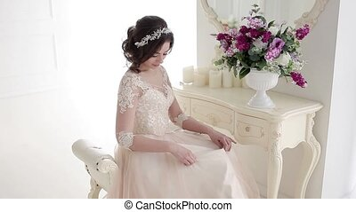 Girl bride adjusts her dress, preparing for the wedding....