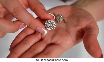 girl bride holding earrings in her hand. close up of...