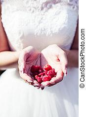 Girl bride holding raspberries in hands summer time joy vertical