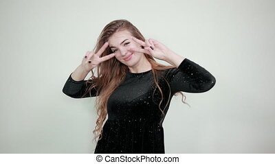 girl brown haired in black dress over isolated white background shows emotions