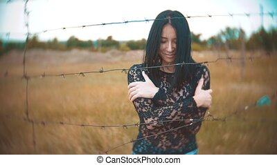 girl brunette refugee behind barbed wire camp lifestyle slow...