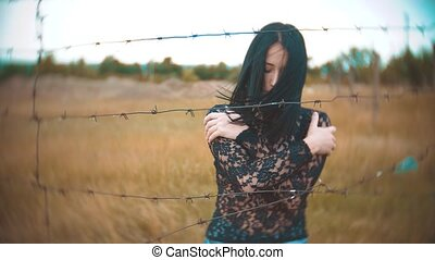girl brunette refugee behind barbed wire camp slow motion...