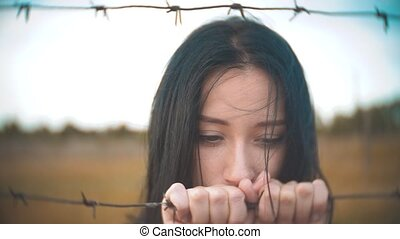 girl brunette refugee behind barbed wire lifestyle camp slow...