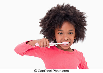 Girl brushing her teeth against a white background