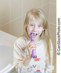 Girl brushing her teeth electric toothbrush with your mouth open.