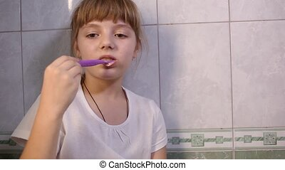 eight-year-old girl in white t-shirt brushes teeth in bathroom. Health care, hygiene and childhood concept. Caries prevention, morning or evening routine