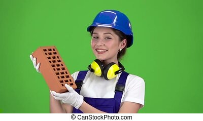 Girl builder carries a brick for construction and shows thumbs up . Green screen. Slow motion. Close up