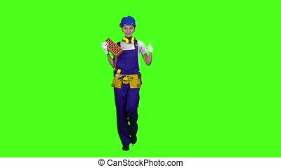 Girl builder carries a brick for construction and shows thumbs up . Green screen. Slow motion