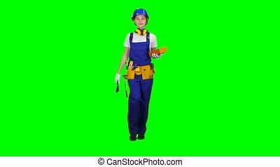 Girl builder carries a brick for construction. Green screen