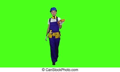 Girl builder carries a brick for construction. Green screen. Slow motion