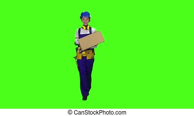 Girl builder carries a cardboard box. Green screen. Slow...