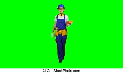 Girl builder in glasses carries a brick for construction. Green screen