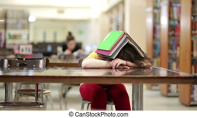 Girl asleep buried under book stack in library reading room