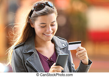 Girl buying on line on the street - Portrait of a happy...