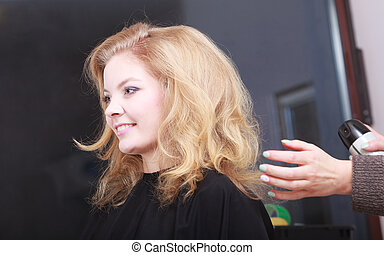 Girl by hairstylist at hair salon