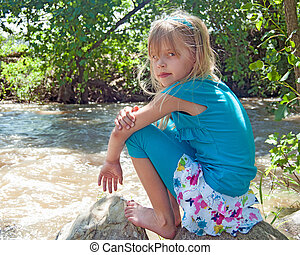 girl by river on a rock