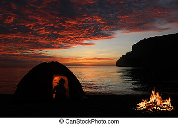 Girl camping alone with campfire on the beach, Red sky sunset background