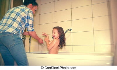 Girl carefully brushing his teeth after eating. Mom teaches her daughter how to clean and rinse your mouth after eating. 4k.