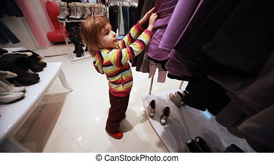 girl carefully choose clothes in shop - cute little girl...
