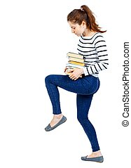 Girl carries a heavy pile of books. back view.